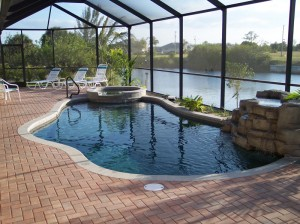 Freeform pool with brick pavers and rock waterfall
