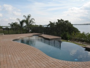 Custom Waterfront Pool with sun shelf, spa and infinity edge