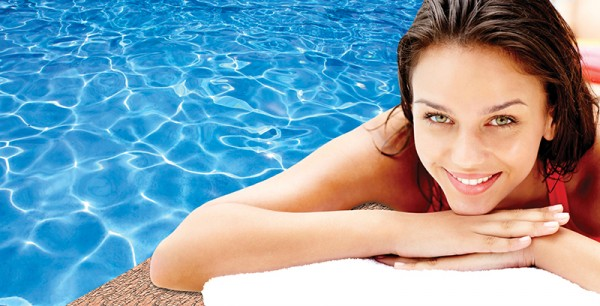 Cute young woman lying relaxed by a swimming pool