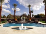 custom in-ground pool with multiple fountains, deck sprayers and flaming urns