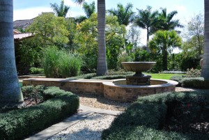 Urn fountain with pebble path and flagstone wall
